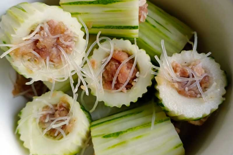Stuffing the cucumbers with pork and noodles