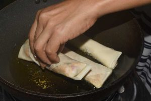 Placing spring rolls in oil