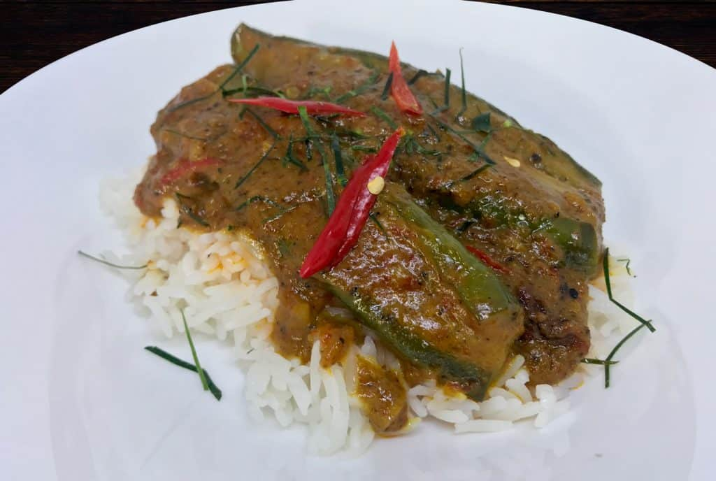 Dry red curry with aubergines on rice